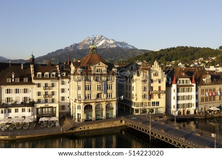 LUCERNE, SWITZERLAND - MAY 07, 2016: Old colorful buildings along the river Reuss are shown in a morning light. Peak of Mount Pilatus can be seen in the distance