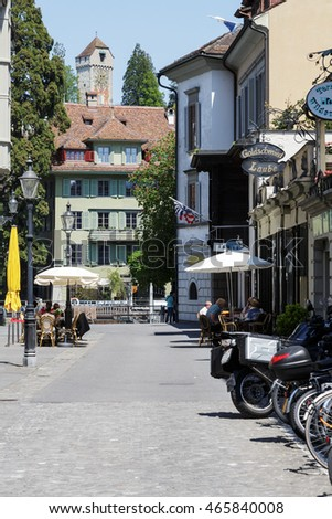 LUCERNE, SWITZERLAND - MAY 08, 2016: Residential building and the tower of stone that is part of old city walls named Musegg can be seen at the end of the street