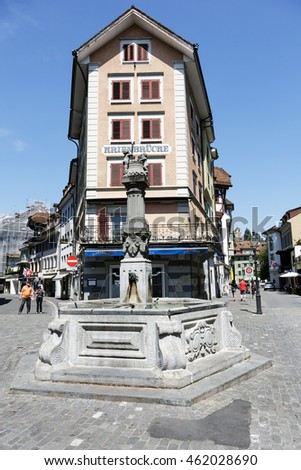 LUCERNE, SWITZERLAND - MAY 08, 2016: Stone fountain in the square in front of the house that is built between two streets. Variety of fountains in the city it is a great tourist attraction.