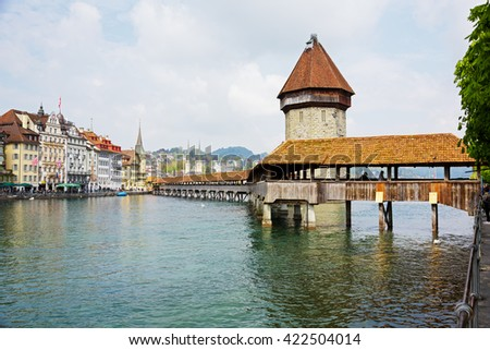 LUCERNE, SWITZERLAND - MAY 02, 2016: The Chapel Bridge (Kapellbruecke) together with the octagonal tall tower (Wasserturm) it is one of the Lucerne's most famous tourists attraction  - stock photo