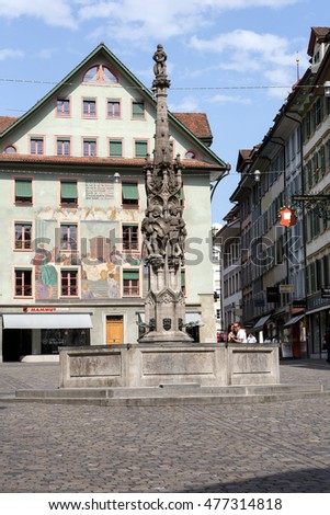 LUCERNE, SWITZERLAND - MAY 10, 2016: Weinmarkt Fountain that is 15th-century fountain and is surrounded by historical buildings decorated with frescoes and it is located at the square in the old town