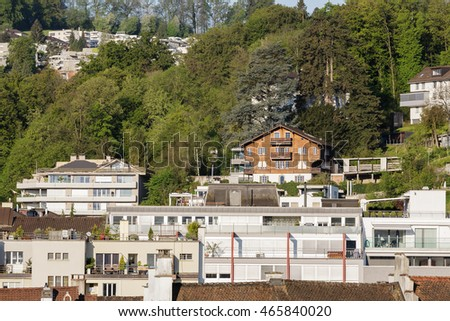 LUCERNE, SWITZERLAND - MAY 07, 2016: Wooden house and brick buildings of the town is shown on a background of green trees that creates a friendly cityscape