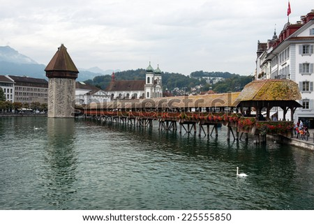 LUCERNE, SWITZERLAND - SEPTEMBER 6, 2014: Chapel Bridge, swans and Jesuit Church, Lucerne. The wooden covered bridge spans the Reuss River with Mt. Pilauts rising in the background