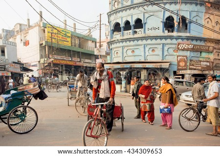 LUCKNOW, INDIA - JAN 31: Elderly cyclist driving on the busy indian street with vehicles and ancient houses on January 31, 2016. Lucknow with population of 6,000,455 is largest city of Uttar Pradesh