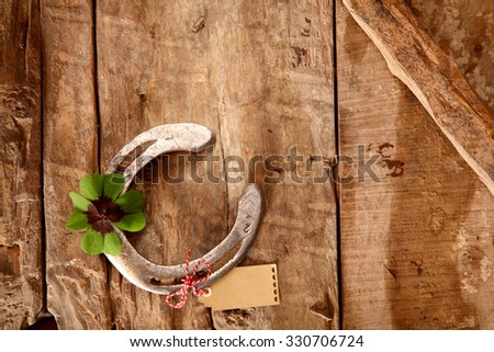 Lucky card background on rustic wood with an old metal horseshoe and green four-leaf clover or Irish shamrock, overhead view with copyspace on the wood - stock photo