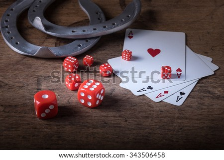 Lucky craps game dice rolling out chance number nine and vintage poker cards with winning aces by old horseshoes for player and gambler good luck charm on rustic wood table in western gambling saloon - stock photo