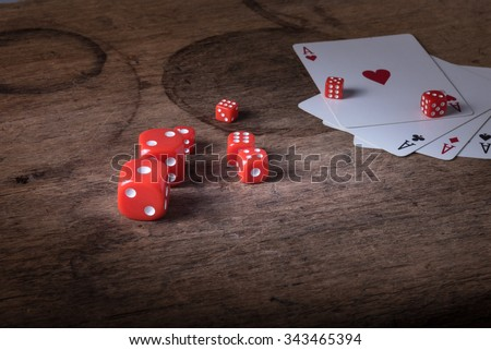 Lucky craps game dices and vintage poker cards with winning aces and gambler good luck charm on rustic wood table in western gambling saloon - stock photo