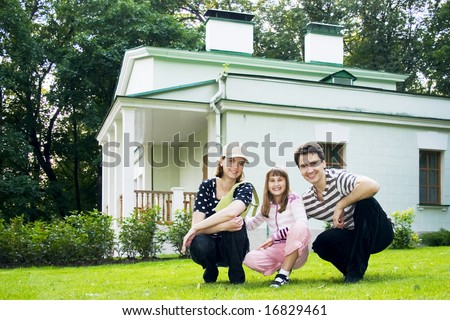Lucky family on lawn beside its building