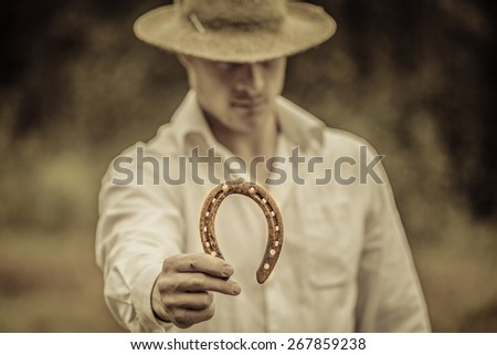 Lucky Farmer Holding a Horseshoe in his right hand - stock photo