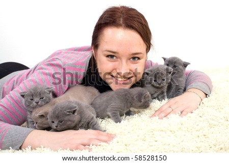 Lucky girl lying on the carpet with her kittens.