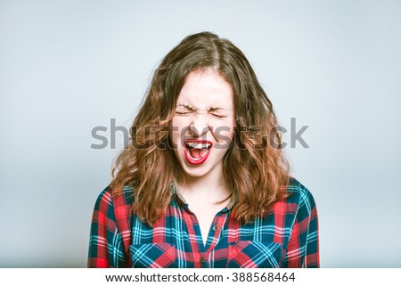 Lucky girl. Portrait of a young woman exults and screams, isolated on a gray background