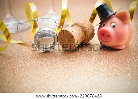 Lucky pig and cork from champagne bottle in front of two glasses - stock photo