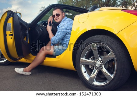 Lucky young man sitting in his new convertible car. Low angle view - stock photo