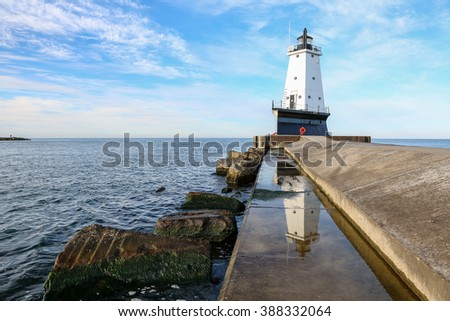 Ludington North Breakwater Pier light - The lighthouse is reflected in standing water on the pier walkway. Moss clings to rocks in the foreground and clouds swirl through the blue sky above. - stock photo