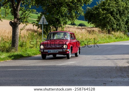 LUDROVA, SLOVAKIA - JULY 25: A classic oldtimer car Skoda 100 passing a junction near Ludrova on July 25, 2009. It was the first Skoda car being produced over a million units. - stock photo