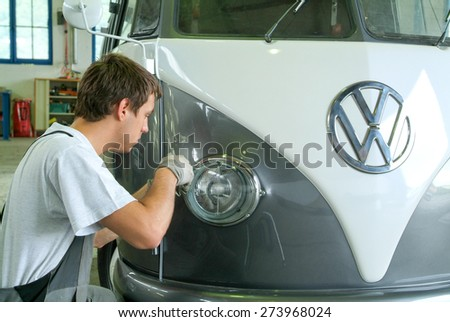 Lugano, Switzerland 25 March 2010: Portrait of an auto mechanic at work on a car in his garage - stock photo