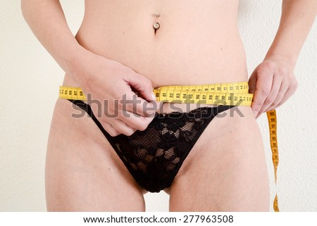 Lugano, Switzerland - 11 May 2015: Close up of female hands measuring waist with measuring tape - stock photo
