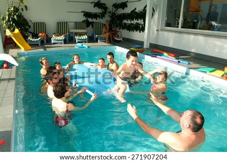 Lugano, Switzerland - 12 November 2004: Adorable babys enjoying swimming in a pool with with their relatives, early development class for infants teaching children to swim and dive