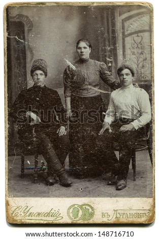 LUGANSK,RUSSIAN EMPIRE - CIRCA 1900s: Studio portrait of young woman and two men, photo studio by S. Umansky, Lugansk, Ukraine, 1900s