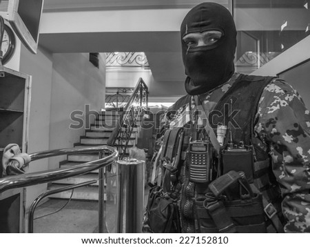 LUGANSK, UKRAINE - April 21, 2014: Pro-Russian  masked fighter guards the entrance inside the building of the Security Service of Ukraine, the captured terrorists.  - stock photo