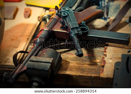 Luger pistol and mashinegun MP 38 in gunsmith on old wooden surface. instagram image retro style - stock photo