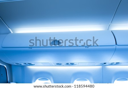 Luggage box in the cabin of the airplane. - stock photo