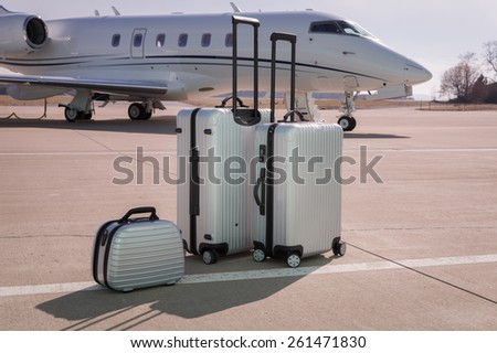 luggage in front of a corporate jet airplane - stock photo
