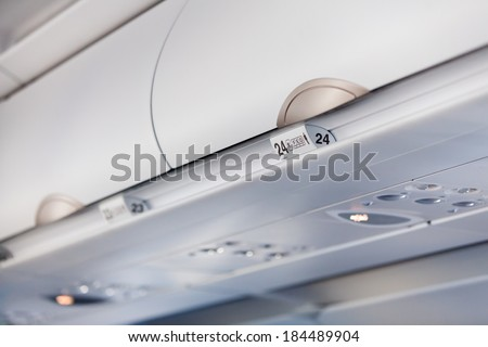 Luggage shells with seat numbers inside the passenger airplane - stock photo