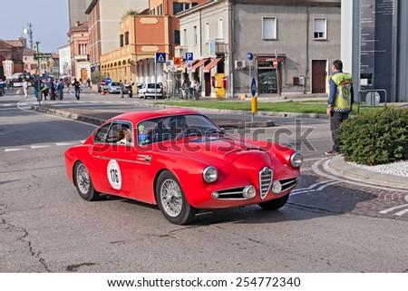 "LUGO, RA, ITALY - SEPTEMBER 21: the crew M. Rivolta A. Zagato on a vintage racing car Alfa Romeo 1900 SSZ (1957) in classic car rally ""Gran Premio Nuvolari"" on September 21, 2014 in Lugo, RA, Italy  - stock photo"