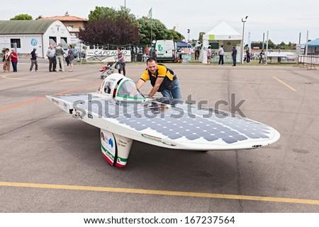 LUGO. RA. ITALY  SEPTEMBER 19: unidentified mechanic moves the solar powered vehicle Emilia 2 at  Expo' AEM-ZERO Alternative Energy for Mobility Zero Emissionon September 19, 2013 in Lugo. RA. Italy - stock photo