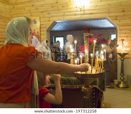 LUHANSK, UKRAINE - June 8, 2014: A woman lights a memorial candle. Orthodox Christians around the world celebrate the day of the Holy Trinity. Trinity Sunday is celebrated on fiftieth day after Easter