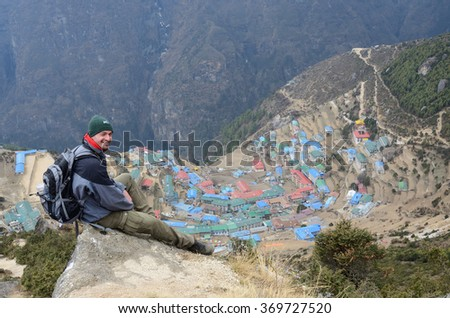 LUKLA,NEPAL - APRIL 17,2013:Unidentified young trekker sitting above Namche Bazaar on his way to Everest Base camp on 17 April,2013 in Namche Bazaar,Nepal.Its main trading center with police,post,bank