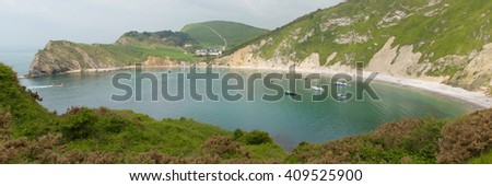 Lulworth Cove Dorset England uk with boats in the natural harbour top tourist attraction on English Jurassic Coast panoramic view - stock photo