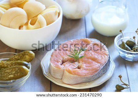 Lumaconi pasta with baked salmon, pickles and capers, italian cuisine. Cooking process. Step 1. Ingredients - stock photo