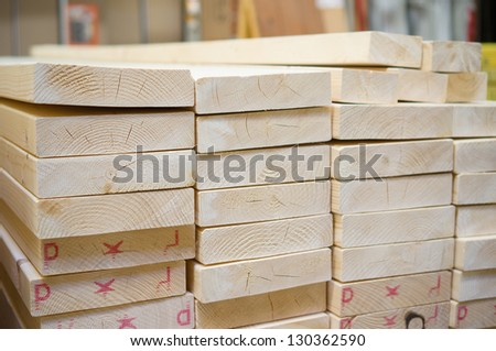 Lumber boards and beams of different sizes lie on racks and pallets in build supermarket - stock photo