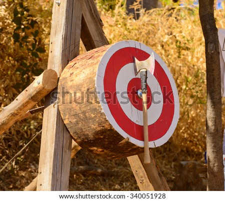 Lumberjack Axe throwing competition with axe stuck in target - stock photo