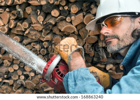 lumberjack close up with chainsaw, forest worker in action - stock photo