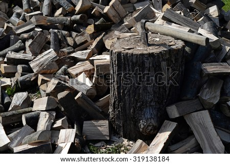 lumberjack hatchet on pile of wood and timber in forest. Cleaning in the garden and cutting fire wood - stock photo