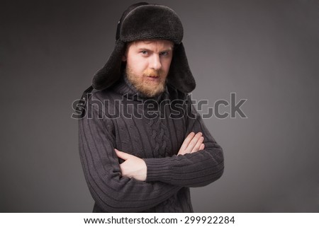 lumberjack in Russian hat, gray background.  looking at camera