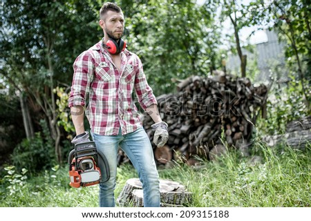 lumberjack or woodcutter moving and looking with chainsaw for trees to chop - stock photo
