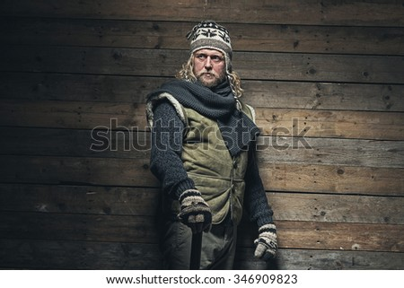 Lumberjack Winter Fashion Man Long Blonde Hair and Beard. Holding Wooden Hammer. Standing in Barn.