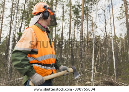 Lumberjack with an axe on the forest background - stock photo