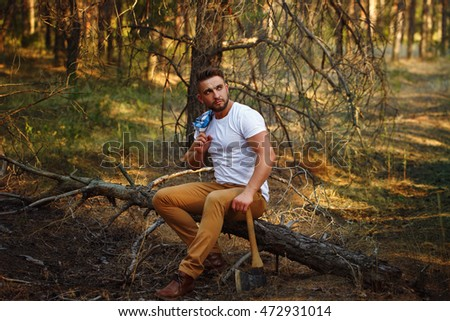 Lumberjack with hatchet sitting on a fallen tree. Woodcutter in a white T-shirt. Felling trees. Logging. Manual labor.