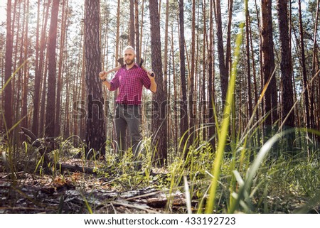 lumberjack with two axes in the woods