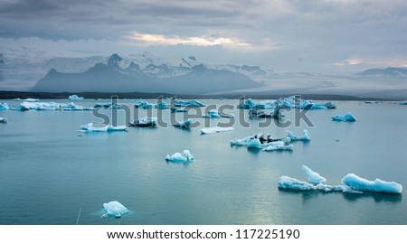 Luminous blue icebergs floating in Jokulsarlon glacial lagoon at dusk, Iceland - stock photo