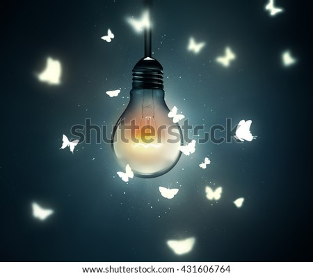 luminous bulb and butterflies flying on light - stock photo