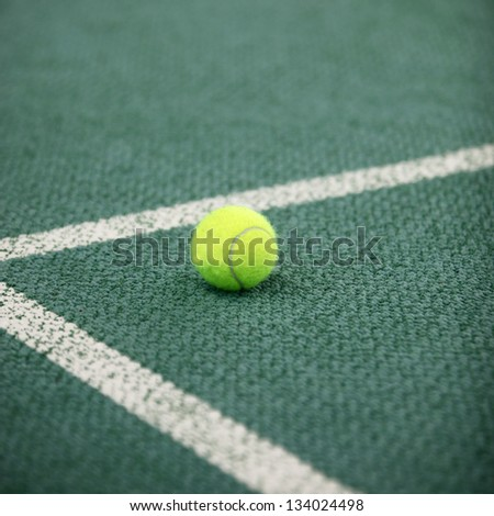 Luminous green high visibility tennis ball on a green tennis court lying in the angle of the lines forming the corner - stock photo