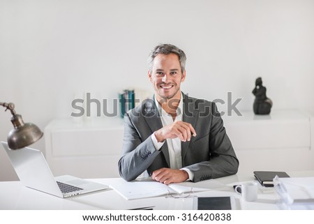 Luminous portrait of a middle age businessman with grey hair wearing a grey suit. He is sitting at his desk, looking at camera while working on some ideas like a communication or creative manager - stock photo