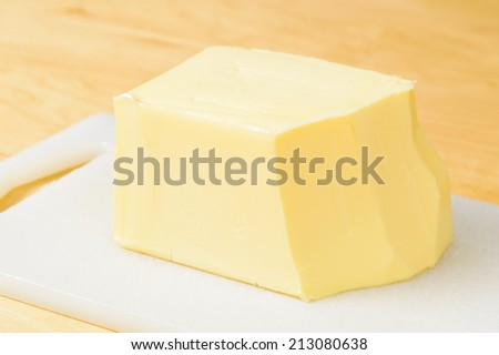 Lump of rich yellow butter on plastic cutting board.