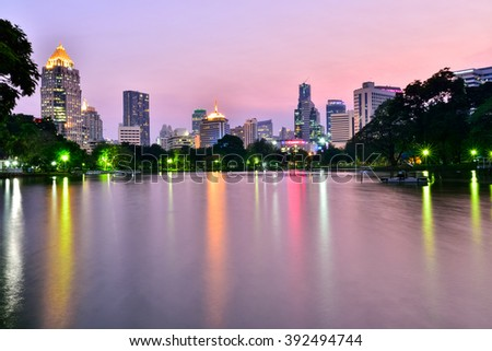 lumpini park  on 17 Mar 2016. Business district cityscape from a park with twilight time , Bangkok Thailand
